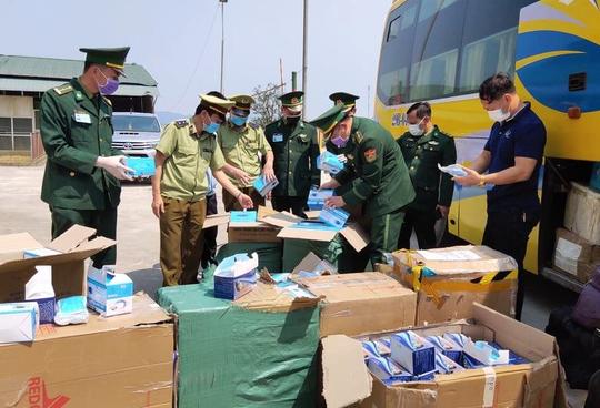 Xe khách vận chuyển gần 30.000 khẩu trang y tế, 98 bộ đồ bảo hộ y tế từ Việt Nam sang Lào - Ảnh 1.