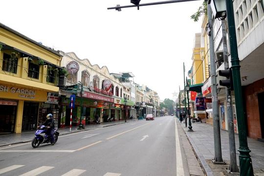 Người dân hạn chế ra đường trong dịch Covid-19, đường phố Hà Nội vắng như Tết - Ảnh 8.