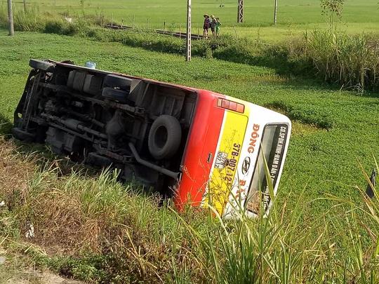 Va chạm với xe ôtô con, xe buýt mất lái lao xuống ruộng lật nghiêng - Ảnh 1.