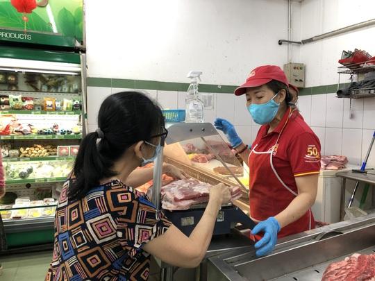 Mùng 5 Tết, người dân TP HCM mua trữ hàng hóa, giá thịt heo đã giảm - Ảnh 1.