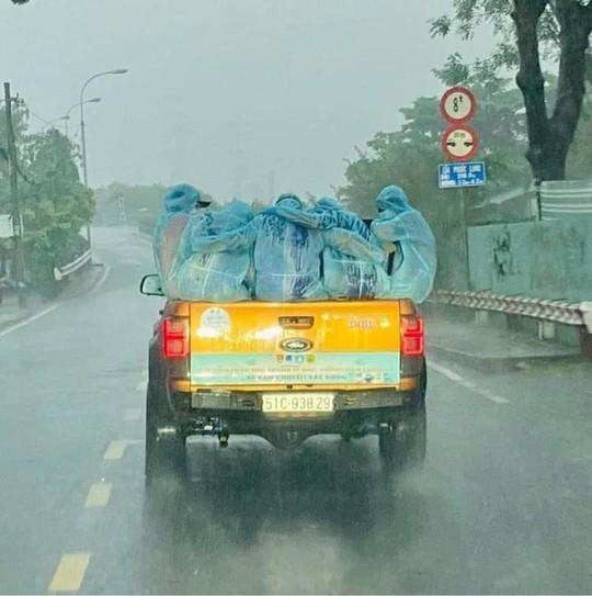 Đội phun xịt khử khuẩn choàng tay giữ ấm nhau dưới mưa - Ảnh 3.