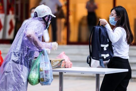 Người dân mặc áo mưa tiếp tế lương thực vào trung tâm thương mại bị phong toả - Ảnh 4.