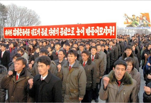 Các công nhân Triều Tiên giơ cao biểu ngữ tuyên thệ trung thành với Kim Jong-un ngày 20-12. Ảnh: Korea Central News Agency