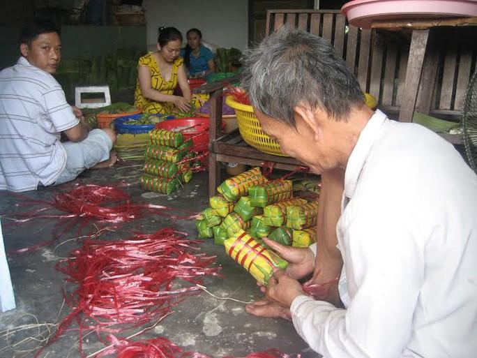 Các thành viên trong gia đình dì Chín cùng nhau gói bánh, trong đó những người đàn ông mạnh tay sẽ đảm nhận khâu cột đòn bánh