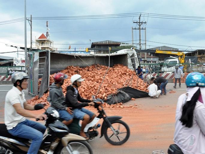 Do né hai thanh niên đi xe máy bị té phía trước, tài xế xe tải chở đầy gạch đánh lái mạnh né tránh khiến xe lao vào dải phân cách rồi lật nhào.