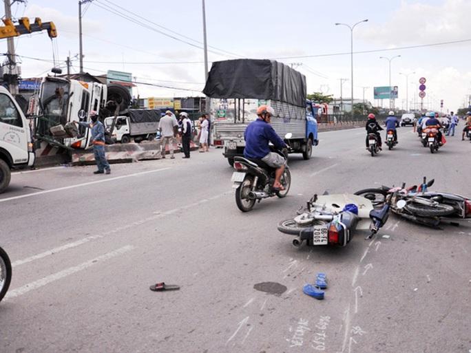 Hai xe máy va quẹt nhau cùng té ngã do mải mê xem vụ xe tải lật.