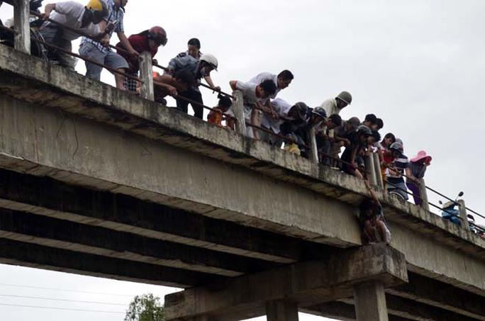 Người hiếu kỳ đứng xem chật kín trên cầu Tân Hạnh và hai bên bờ sông