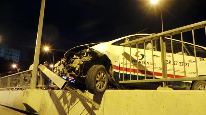 Chiếc xe taxi trèo lên phần đường dành cho người đi bộ trên cầu chữ Y (quận 5), một phần đầu xe lao ra khỏi cầu suýt rơi xuống rơi xuống bên dưới.