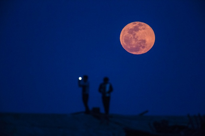 Người đàn ông đang chụp ảnh trăng máu ở khu vực ngoại ô Thượng Hải - Trung Quốc. Ảnh: Reuters