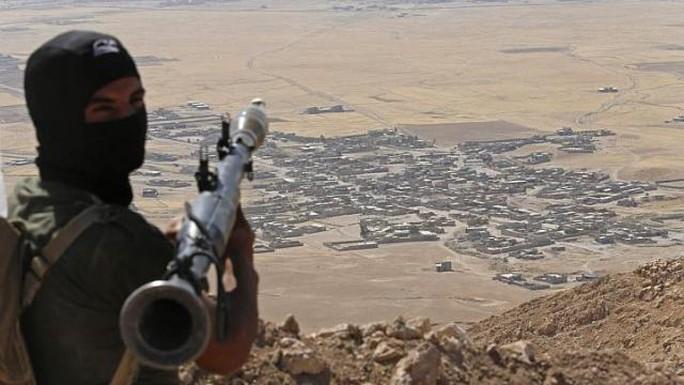 Một tay súng người Kurd quan sát làng Baretle – đang nằm trong tay IS. Ảnh: Reuters