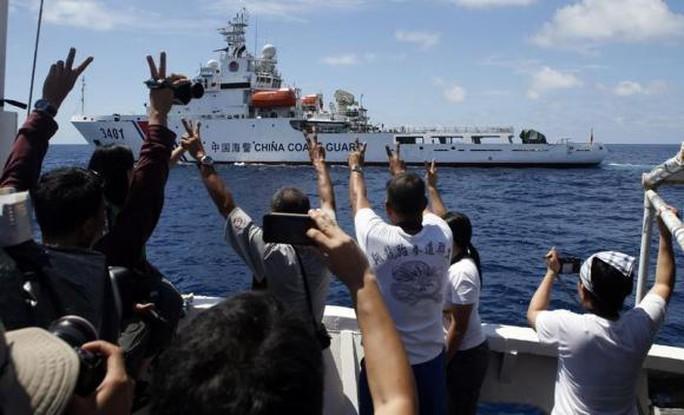 Những người trên tàu tiếp tế Philippines giơ dấu chữ V sau khi thoát khỏi tàu hải giám Trung Quốc. Ảnh: Reuters