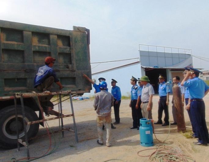 Lực lượng chức năng đang tiến hành cắt thùng xe hổ vồ vượt chiều cao cho phép