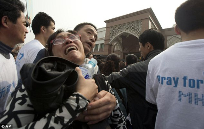 Distraught: A woman weeps as she joins the crowd massed outside the embassy in Beijing