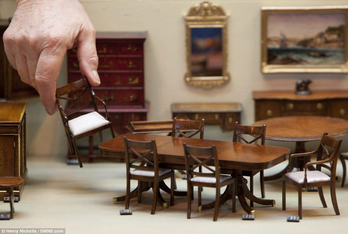 For sale: The woman carefully places a miniature chair inside the house. Other tiny creations inside the property include tables, dressers, paintings and cabinets