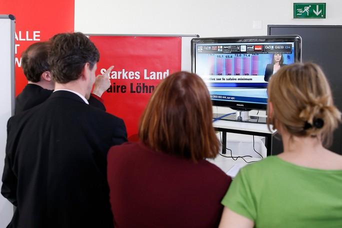 Người dân Thụy Sĩ xem kết quả bỏ phiếu về mức lương tối thiểu hôm 18-5. Ảnh: AP