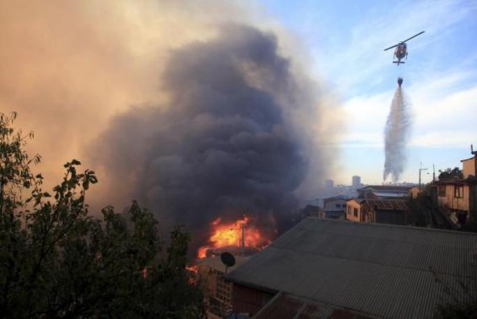 Trực thăng xả nước dập tắt đám cháy. Ảnh: Reuters