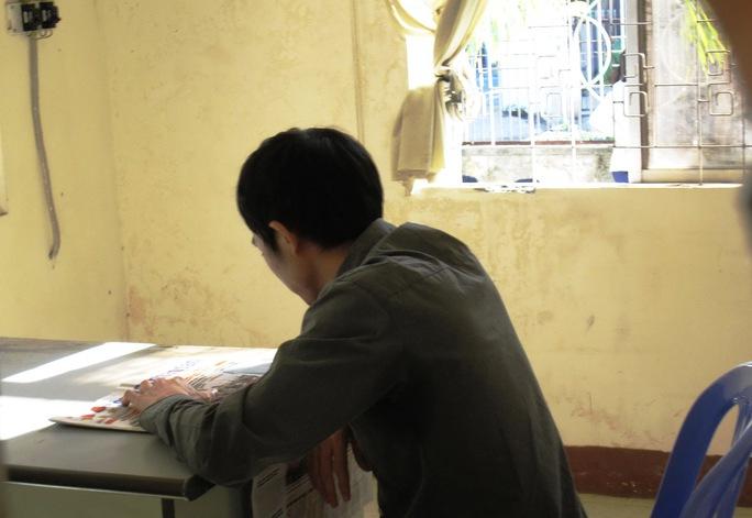 Bị cáo Nguyễn Thân Thảo Thành, người được cho là dùng dùi cui đánh vào đầu gây tử vong Ngô Thanh Kiều, thản nhiên ngồi đọc báo trong giờ giải lao tại tòa