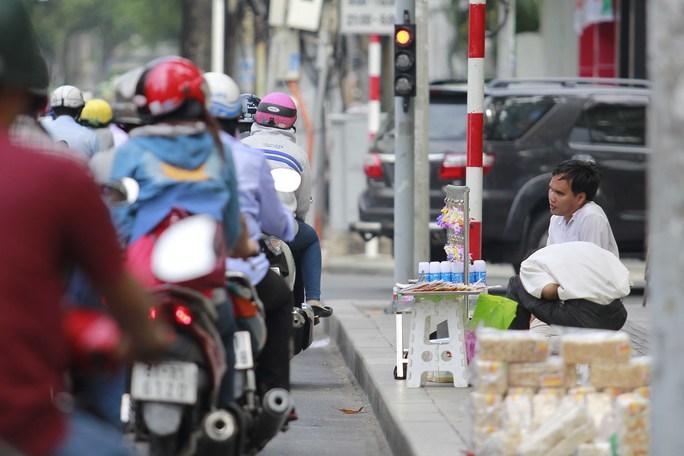 Một người khuyết tật bán tăm bông ngay ngã tư Nguyễn Thị Minh Khai-Nam Kỳ Khởi Nghĩa, quận 1 - Ảnh: Hoàng Triều