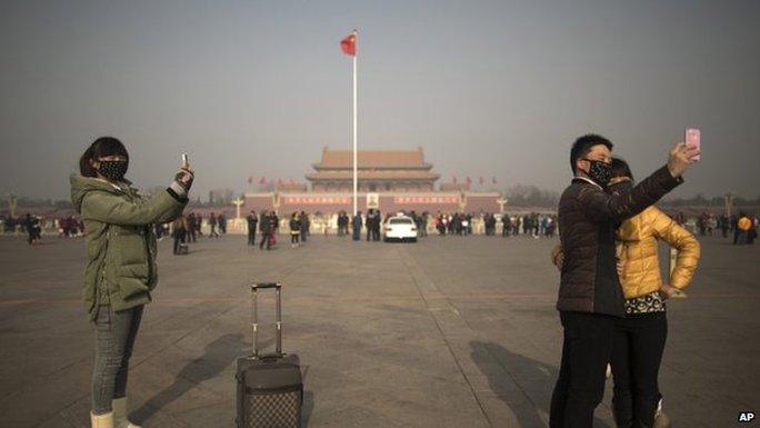 Giới chức Trung Quốc khuyên người dân ra đường nên đep khẩu trang. Ảnh: AP