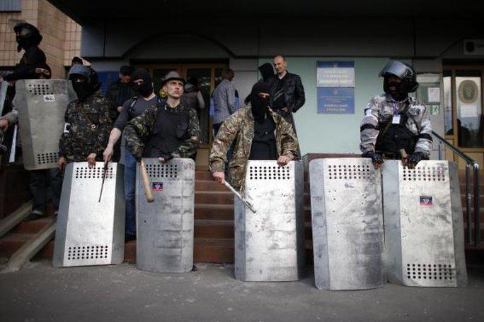 Các phần tử ly khai thân Nga đứng gác trước lối vào tòa nhà hội đồng quận ở Donetsk, Đông Ukraine hôm 4-5. Ảnh: Reuters