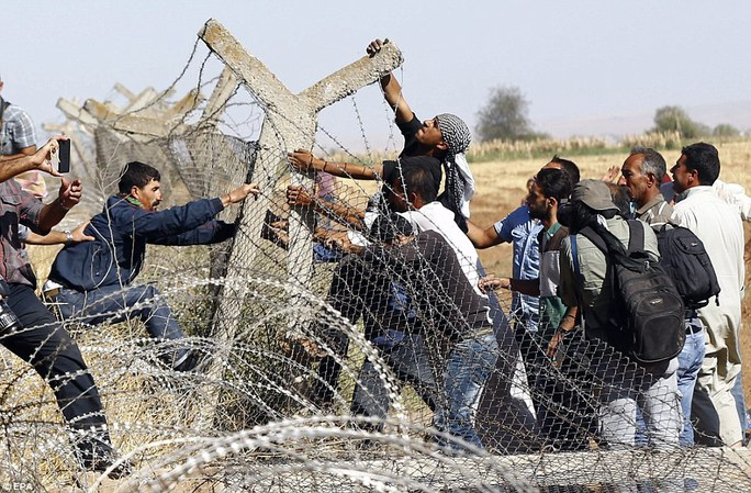 Người Kurd xô đổ hàng rào ở biên giới Thổ Nhĩ Kỳ, đòi gia nhập lực lượng chống IS ở Kobane. Ảnh: EPA