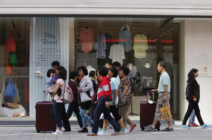 Du khách đi bộ trên đường phố Nhật. Ảnh: Reuters
