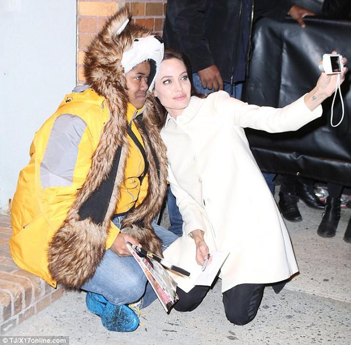 Angelina Jolie quỳ xuống sàn vỉa hè, an ủi và chụp ảnh cùng một người hâm mộ