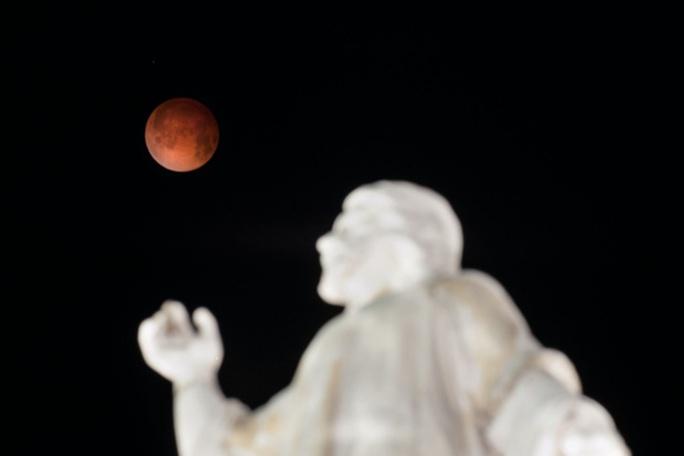 Trăng máu chụp từ tượng đài El Salvador del Mundo tại San Salvador, Mỹ