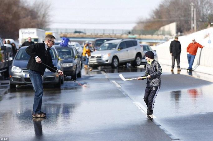 Hai cha con chơi khúc côn cầu giết thời gian trong lúc kẹt xe