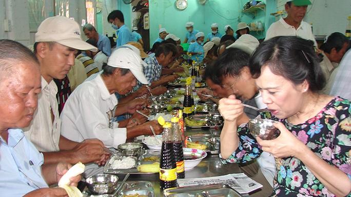 Bà Mai Thị Hạnh (bìa phải) dùng cơm với người nghèo trưa 4-7 - Ảnh: M.Hương