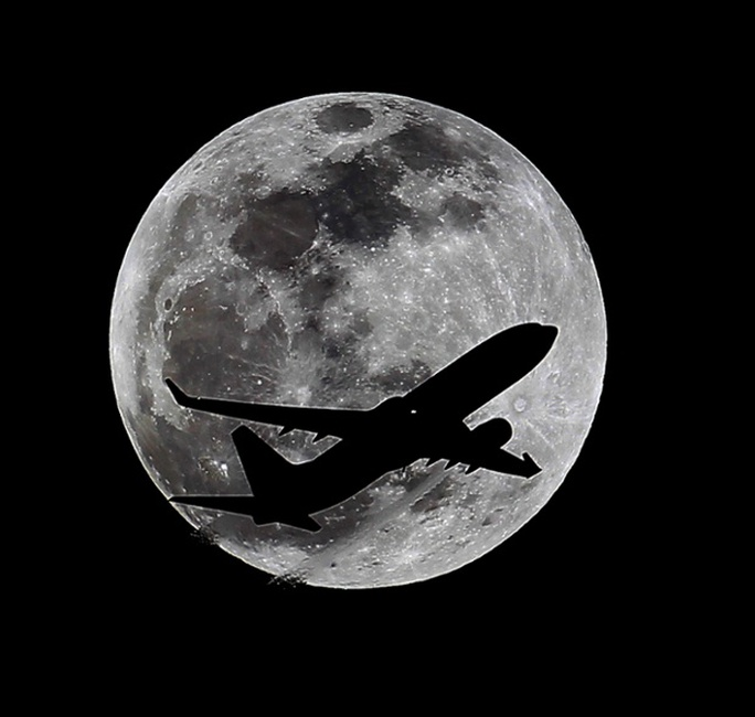 A plane crosses the moons path over Whittier, California, approximately one hour before the total lunar eclipse. Photograph: Nick Ut/AP