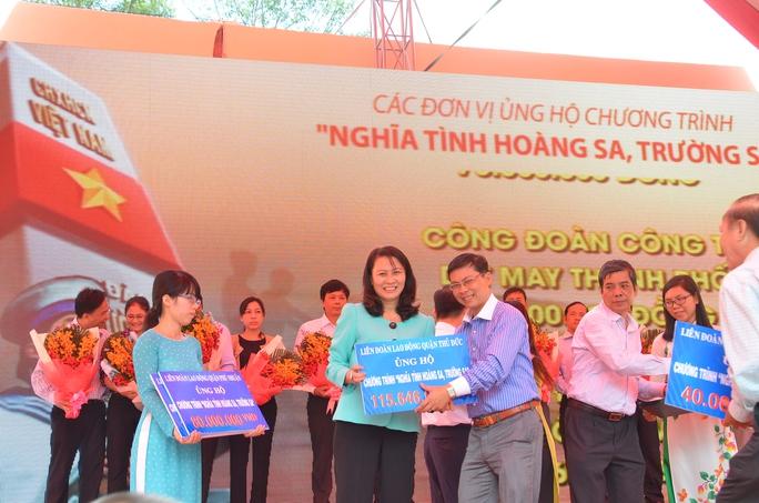Bà Nguyễn Thị Thu, Chủ tịch LĐLĐ TP HCM, tiếp nhận tiền ủng hộ từ đại diện LĐLĐ quận Thủ Đức, TP HCM ẢNH: TẤN THẠNH