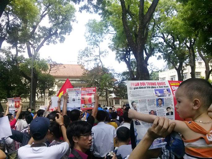 Em bé cùng cha mình giương biểu ngữ, hình ảnh phản đối trước Đại sứ quán Trung Quốc