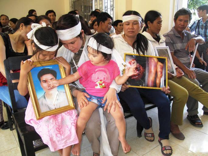 Gia đình bị hại mang theo di ảnh nạn nhân cùng hình ảnh chụp hậu quả việc dùng nhục hình - Ảnh: Hồng Ánh