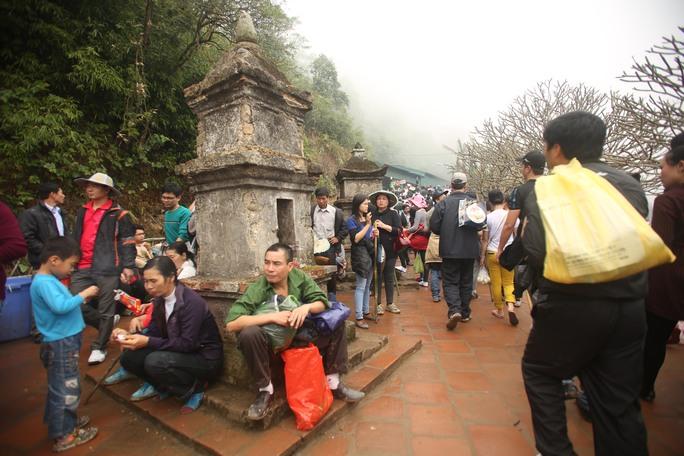 Người dân dự lễ hội nghỉ chân bên những ngôi tháp cổ ở chùa Hoa Yên