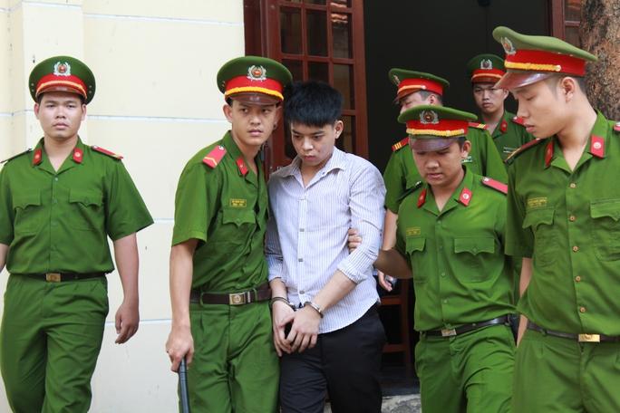 Bị cáo Phạm Thành Đạt bị áp giải ra xe chở về trại giam, sau khi HĐXX tuyên 7 năm tù về tội giết người vào sáng 12-8.