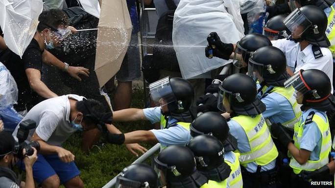 Cảnh sát xịt hơi cay vào người biểu tình. Ảnh: Reuters