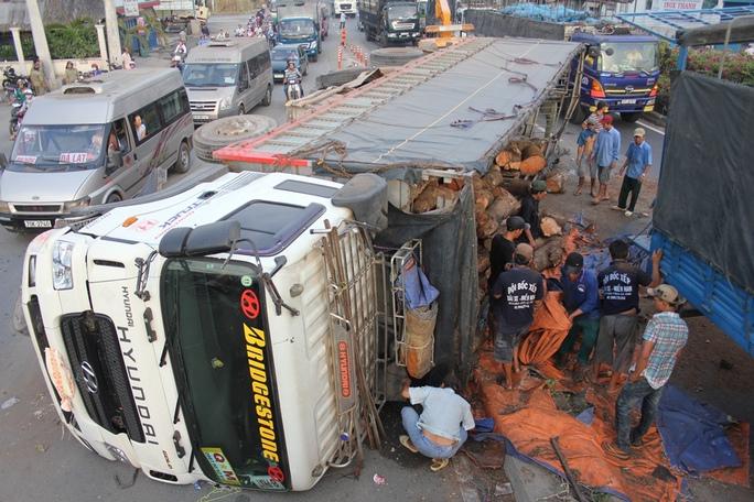 Hiện trường sự cố xe tải chở gỗ lật nhào trên đường