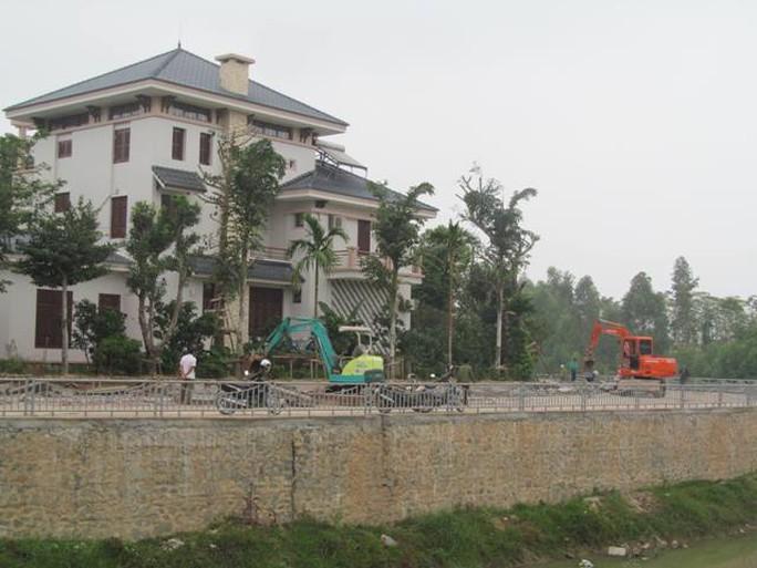 Gia đình ông Hà Hòa Bình chủ động thuê máy móc phá dỡ dãy tường rào được xây dựng trên đất lấn chiếm.