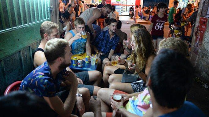 Sau 23 giờ, rất đông khách du lịch ngồi ăn uống từ trong hẻm ra đến vỉa hè đường Bùi Viện, Q.1, TP.HCM - Ảnh: Hữu Khoa
