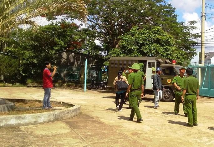 Cảnh sát hỗ trợ tư pháp đưa bị cáo ra xe về trại giam sau khi HĐXX hoãn tòa.