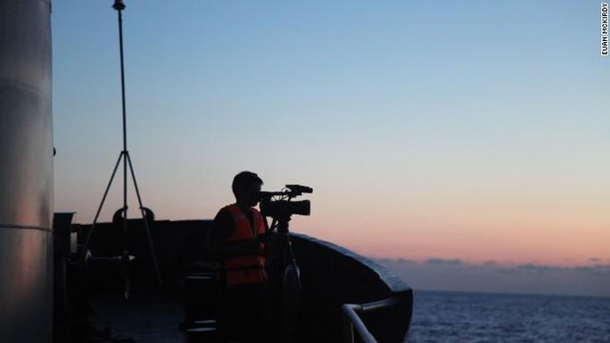 Một phóng viên quay phim từ mũi tàu 8003