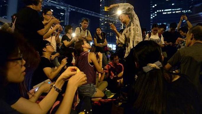 Henry Fung, 30 tuổi, (vị trí trung tâm) đang dạy đám đông người biểu tình cách gấp dù theo phong cách origami để treo lên