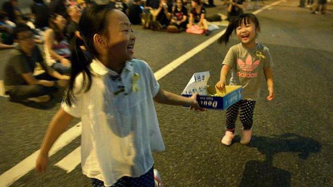 Nụ cười ngây thơ của các em nhỏ theo cha mẹ đi biểu tình. Ảnh: Straitstimes
