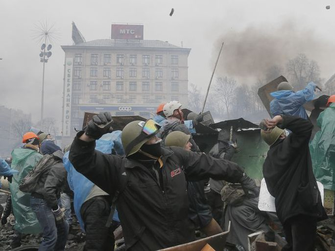 Anti-government protesters throw stones at riot police.