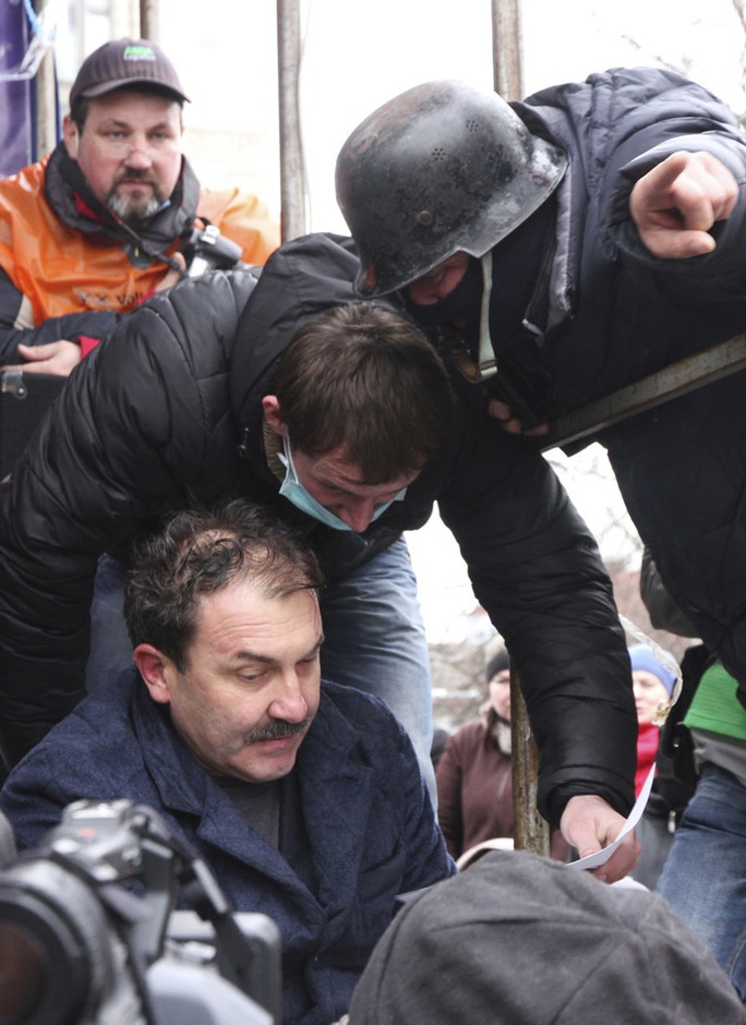 Anti-government protesters capture Volyn Region Governor Alexander Bashkalenko (L, bottom) during a rally in the town of Lutsk in northwestern Ukraine, February 19, 2014. (Reuters/Cathal McNaughton)