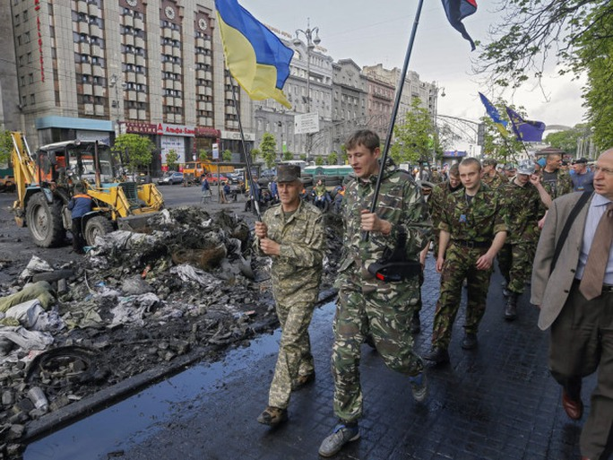 Maydans self-defence members march as Ukrainian communal workers remove a barricade near Independence Square in Kyiv Wednesday.