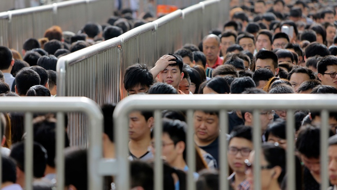 A man looks up as he lines up with other passengers and waits for a security check during morning rush hour at Tiantongyuan North Station in Beijing May 27, 2014 (Reuters / Jason Lee)