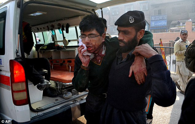 A hospital security guard helps a student injured in a shootout at a military school in Peshawar