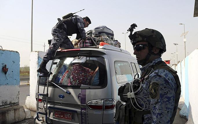Cảnh sát Iraq đang kiểm tra một chiếc xe tiến vào thủ đô Baghdad. Ảnh: AP